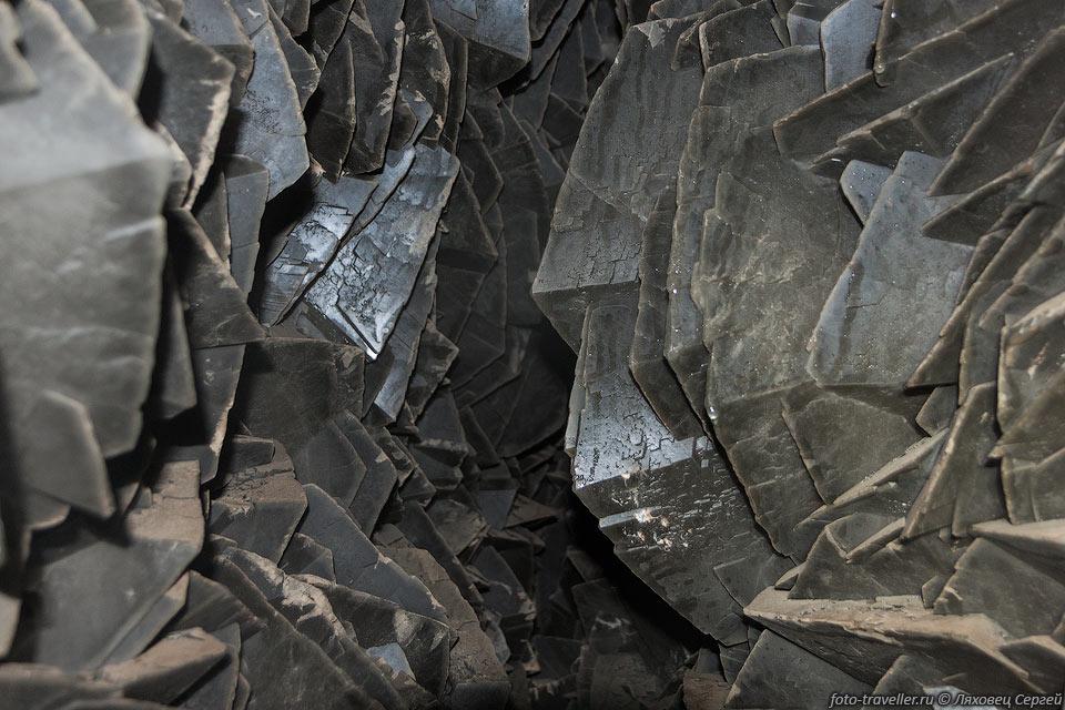 Щетки ромбоэдрических кристаллов кальцита. Кальцит темный из-за множественных включений мелких игл марказита.